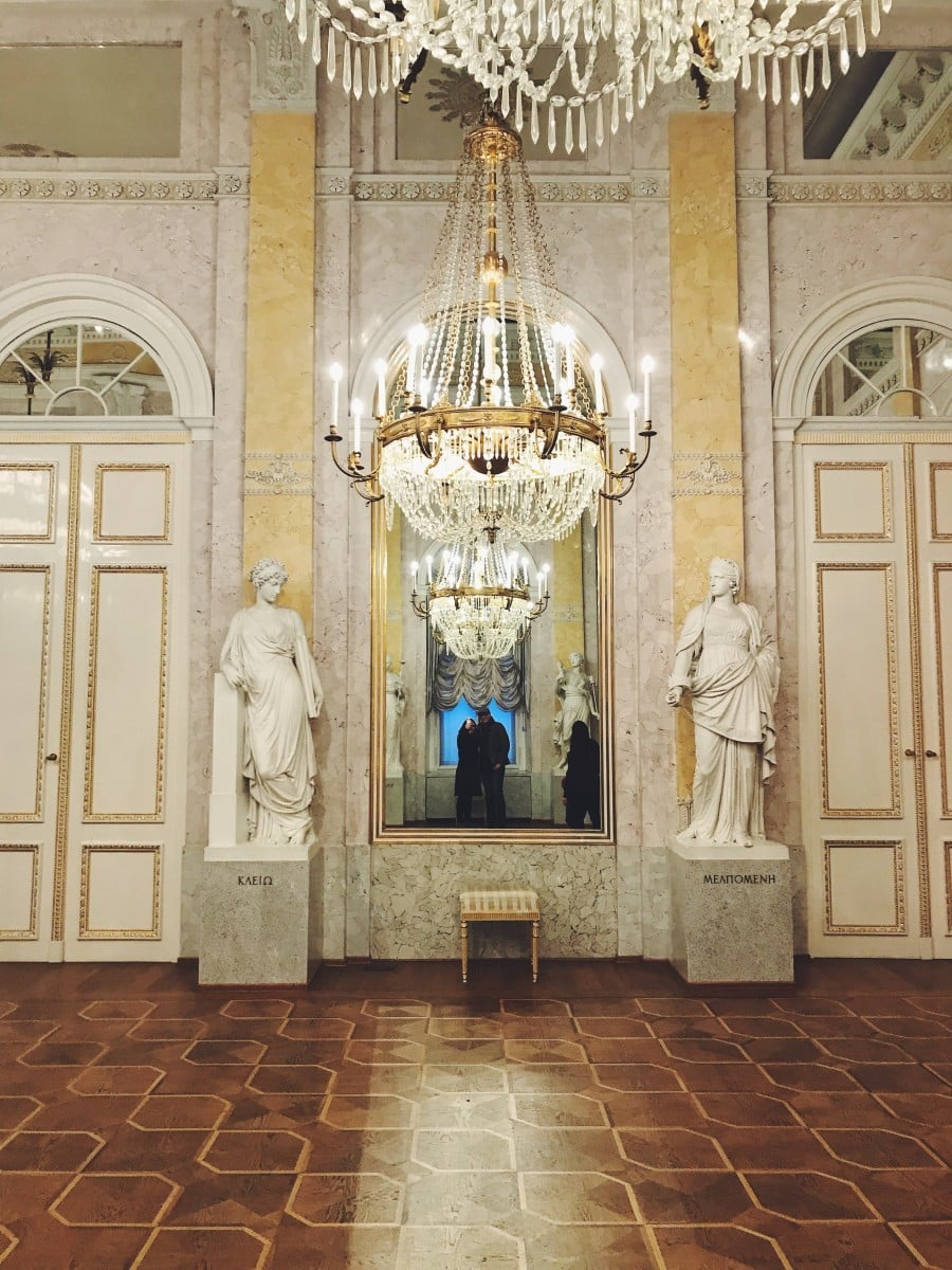 Chandeliers and statues in a palace hall