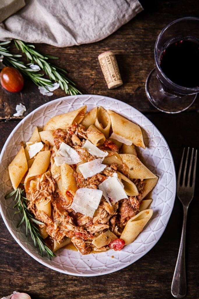 Top down view of the Venetian chicken ragu pata with a glass of wine and a fork