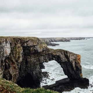 The Green Bridge of Wales over stormy sea