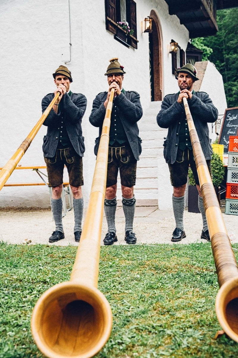 Three alphorn players in lederhosen at Lederhosendonnerstag