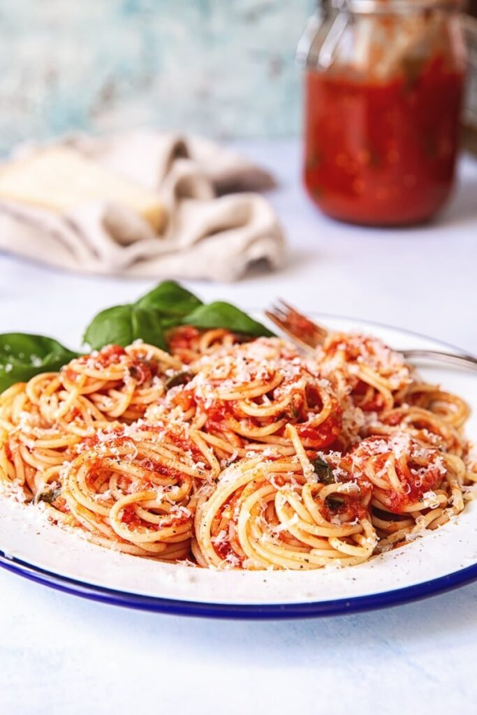 Plate of spaghetti with sauce with jar of sauce in the background
