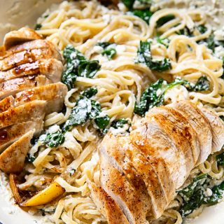 Spinach ricotta linguine with sliced lemon butter chicken in white pan