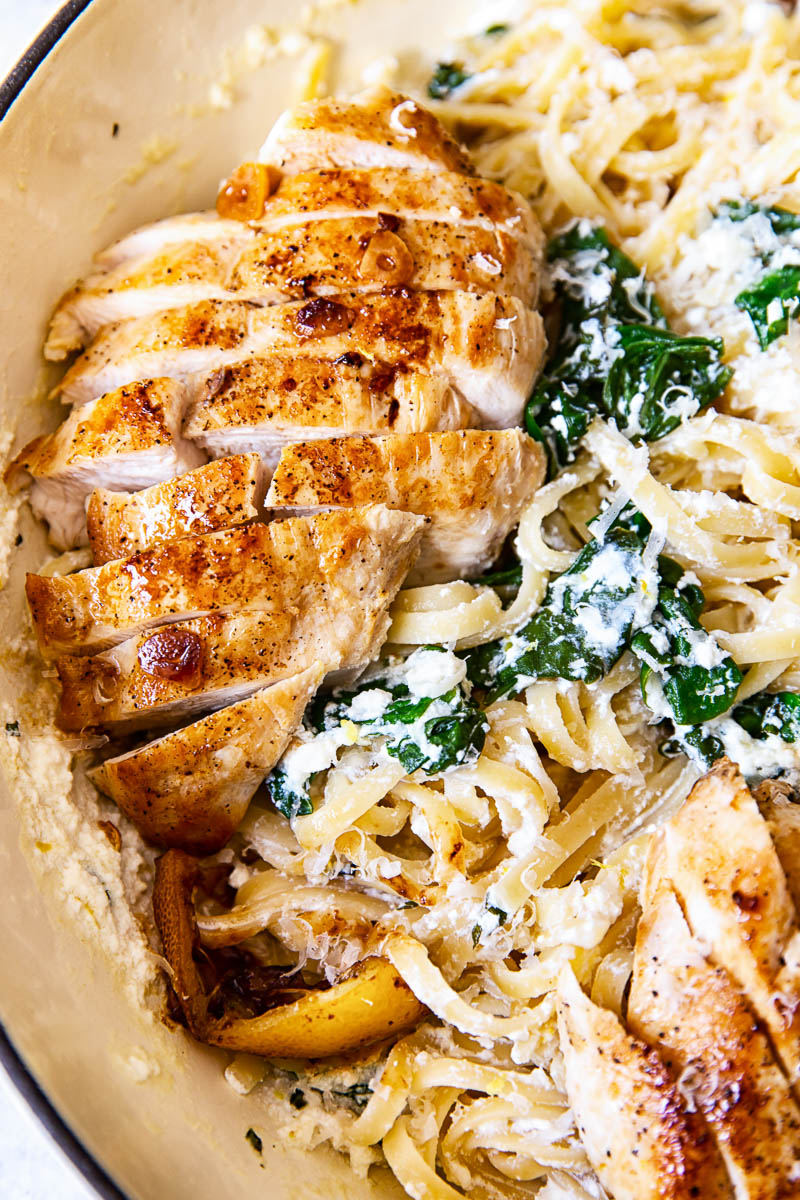Sliced lemon butter chicken breasts on top of spinach ricotta pasta
