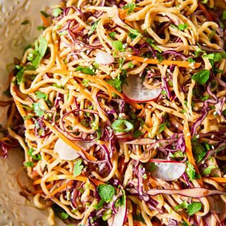 Asian noodle salad with red cabbage, carrots and radishes, sprinkled with green onions and sesame seeds.