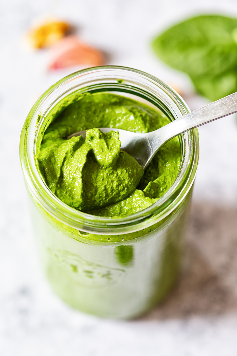 Spinach pesto on a spoon in glass jar. View from top.