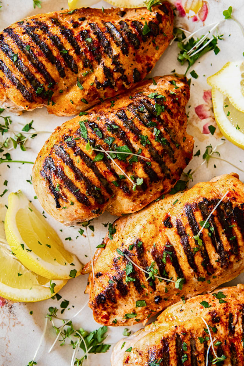 grilled chicken breasts sprinkled with micro herbs and garnished with lemon slices