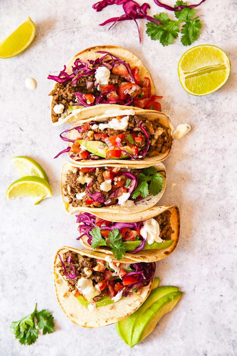 Ground Beef Tacos topped with salsa, avocado slices and red cabbage slaw.