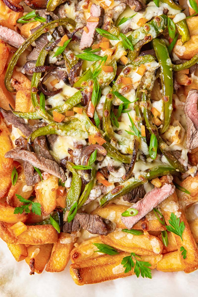 Chunky chips topped with strips of steak, green peppers, onions and melted cheese.