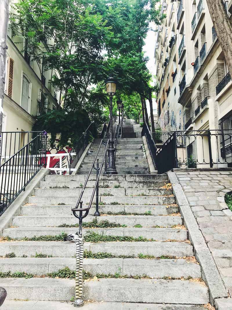 Set of stairs in Montmartre, with buildings at the sides and trees at the top