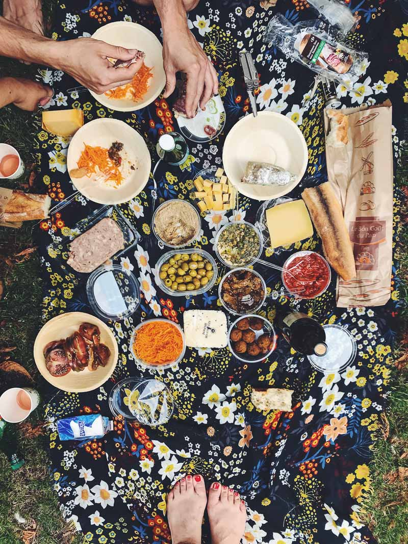 Top down view of a Parisian picnic, with bread, cheese and charcuterie