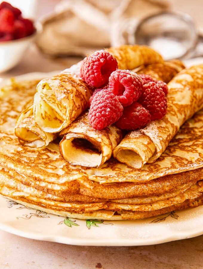Blini stacked on a plate, topped with raspberries.