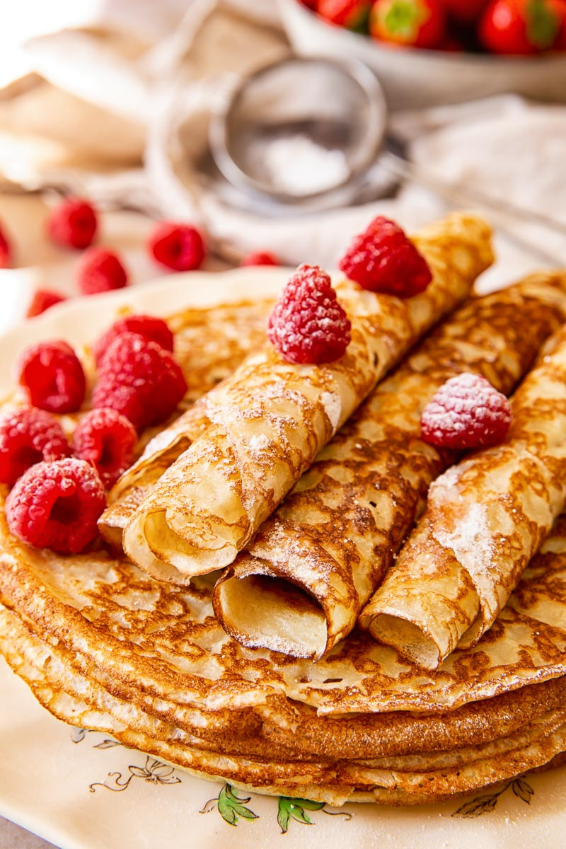 Russian Crepes Blini sprinkled with powdered sugar and topped with raspberries