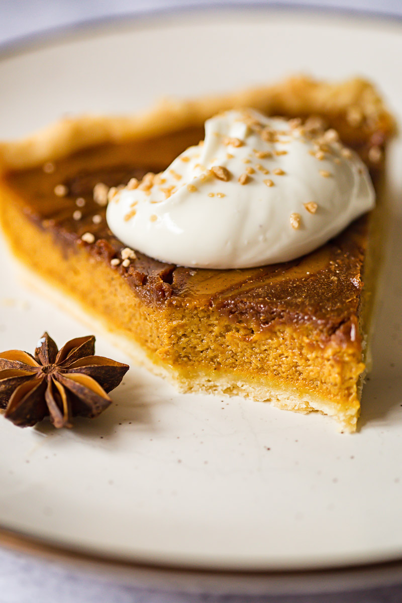 pumpkin pie slice topped with whipped cream and maple sugar