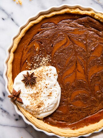 Pumpkin pie with chocolate swirl and whipped cream.