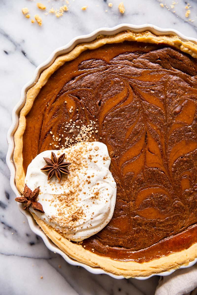 Pumpkin pie with chocolate swirl and whipped cream.