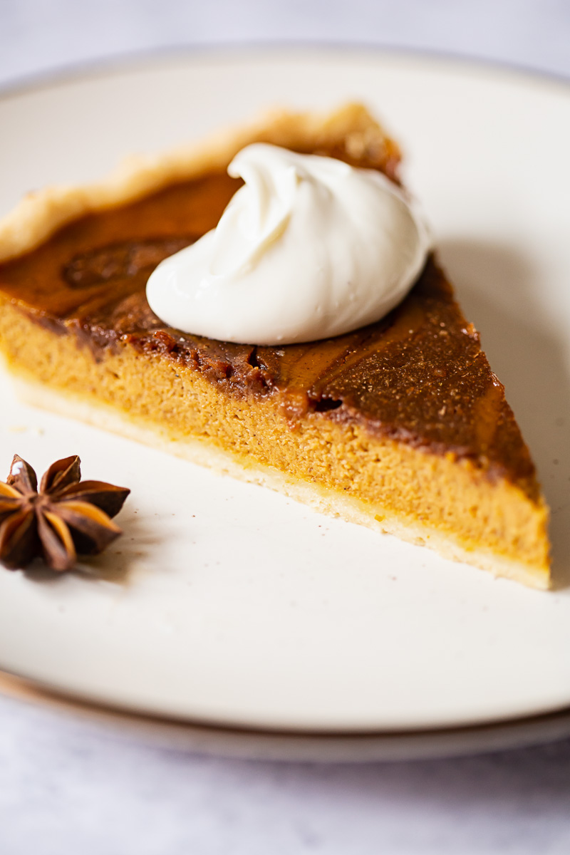 pumpkin pie slice with whipped cream on top