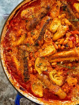Sausages cooked in smoky tomato sauce with white beans and artichokes.