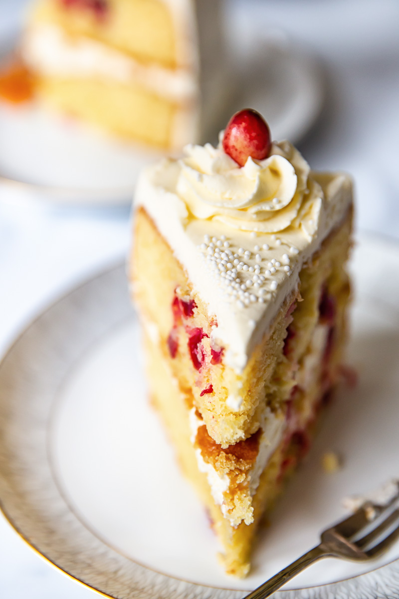 a slice of cranberry cake with a cream cheese frosting rosette on top