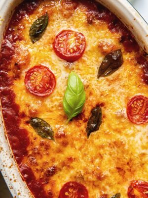 Baked gnocchi topped with melted mozzarella, basil leaves and tomato slices
