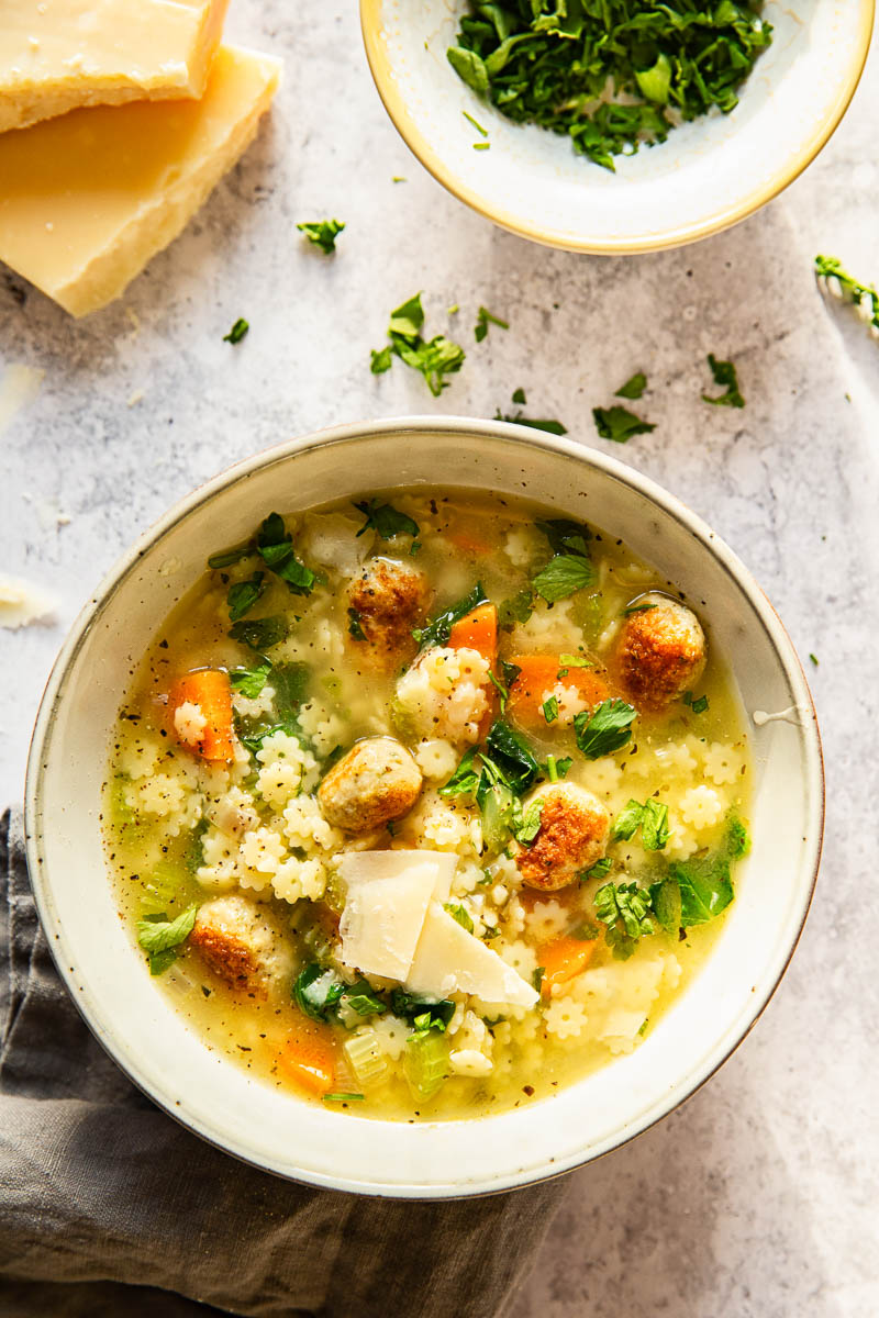 Italian Wedding Soup with chopped parsley and shved Parmesan