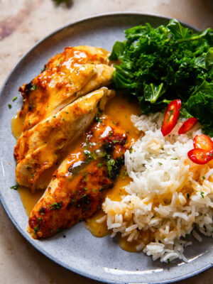 glazed chicken breast, rice and kale on a grey plate