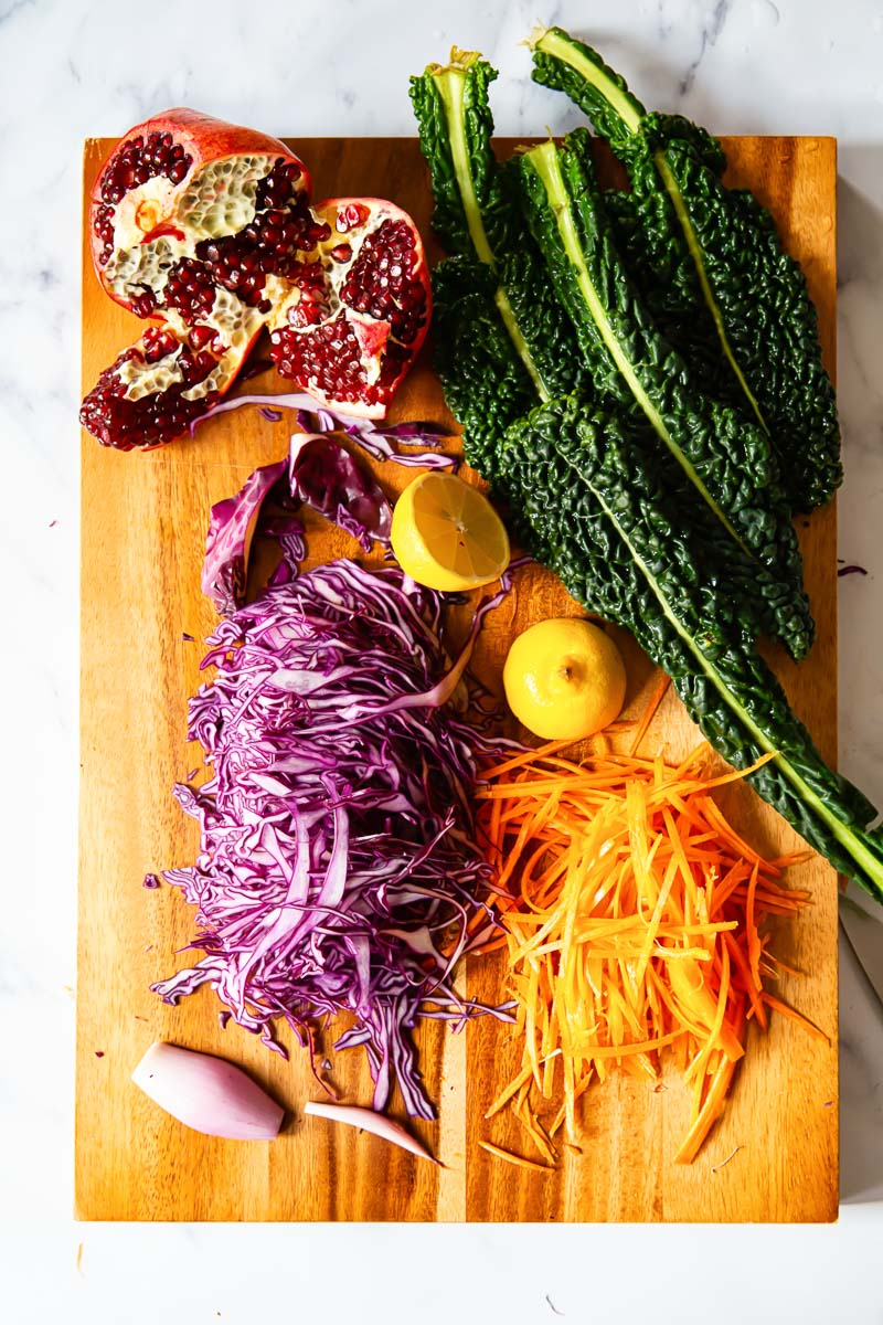 Sliced red cabbage, kale, carrots, pomegranate and shallots on cutting board