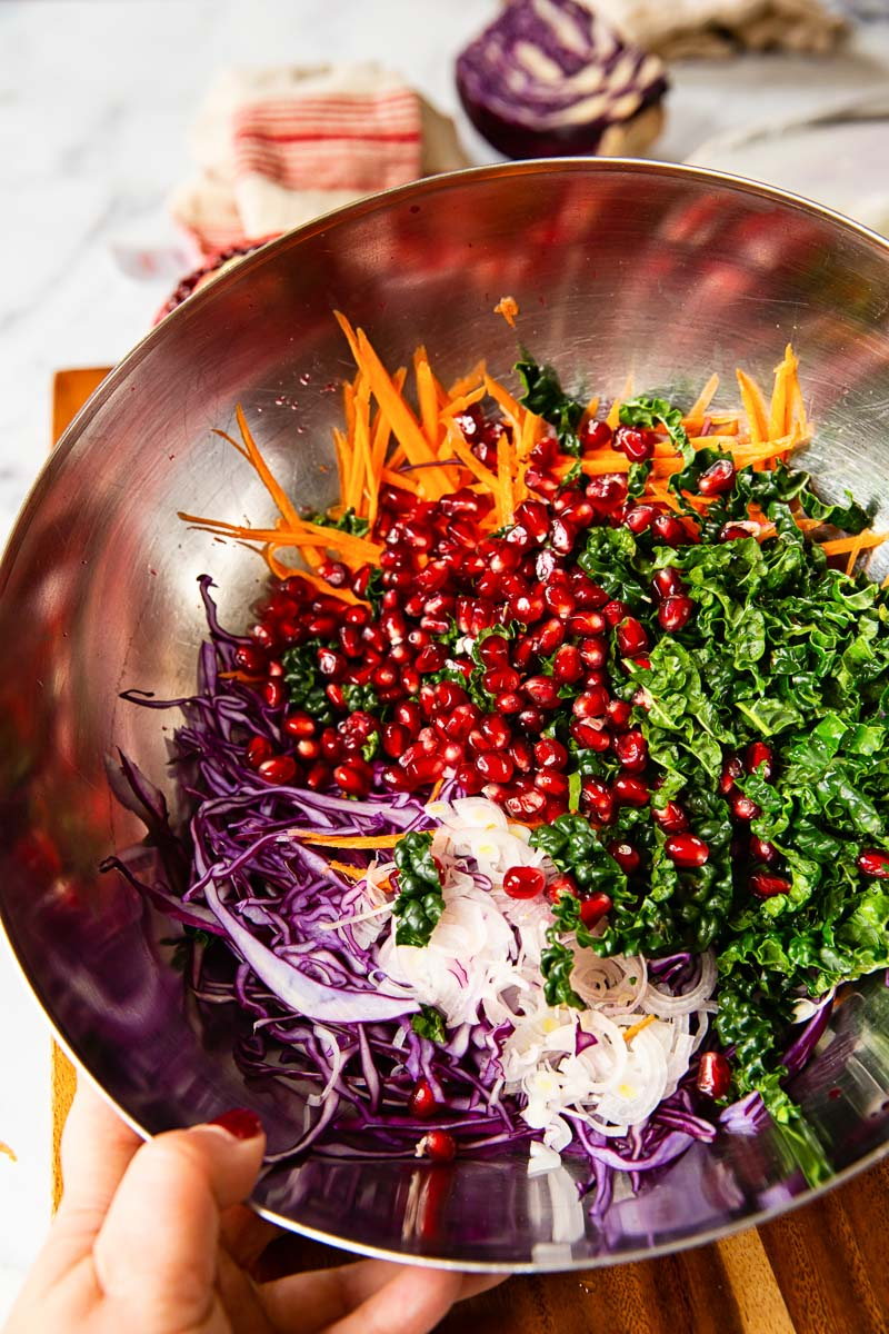 Sliced red cabbage, carrots, kale and pomegranate seeds in a bowl