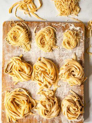 homemade tagliatelle and tagliolini on wooden board