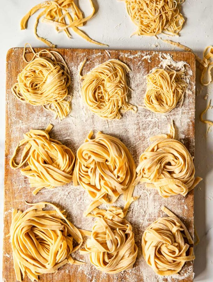 homemade tagliatelle and tagliolini on wooden board