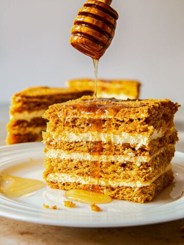 Russian honey cake slice with honey drizzled from above.