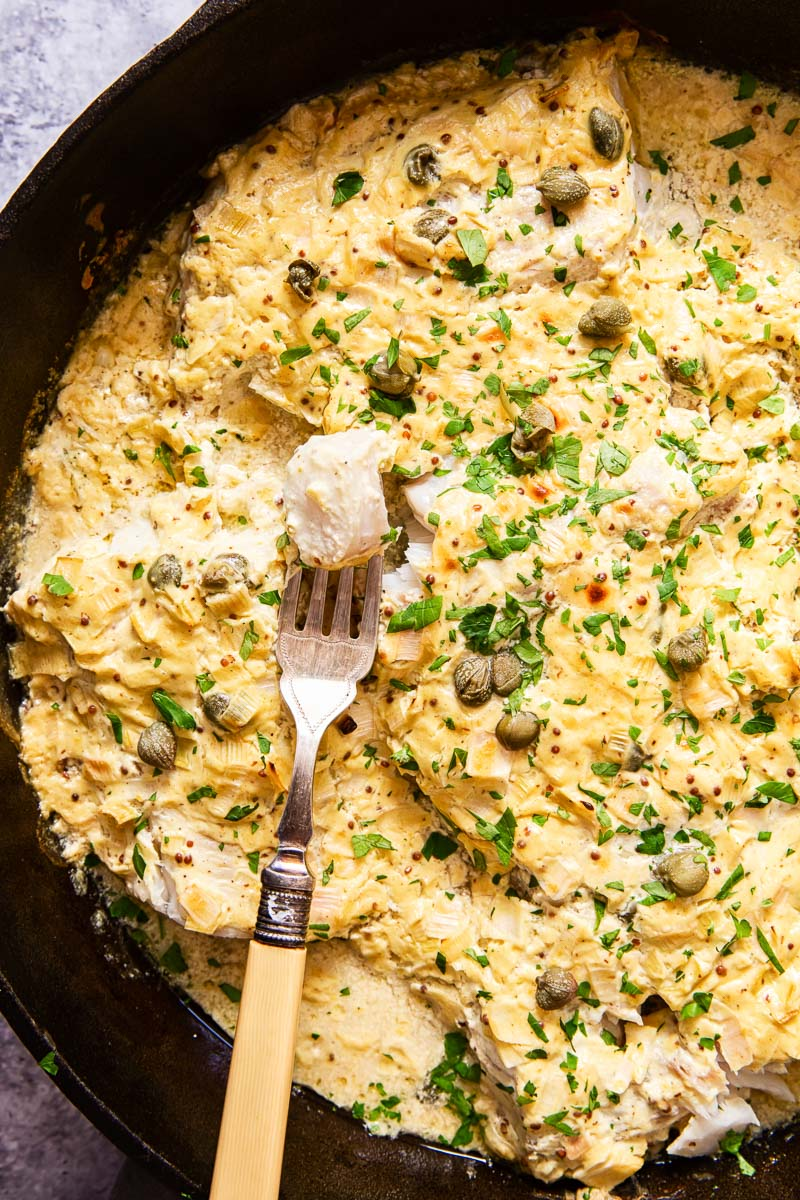 fish under a creamy sauce sprinkled with fresh chopped parsley in cast iron skillet