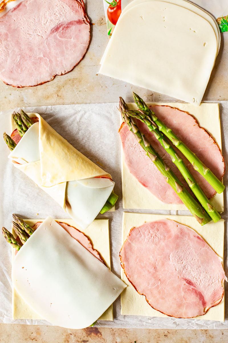 puff pastry squares lined with slices of ham, cheese and asparagus