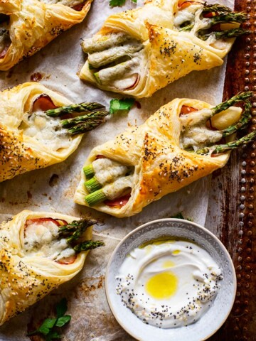 cheese and asparagus puff pastry pockets on baking sheet a small dish with dip