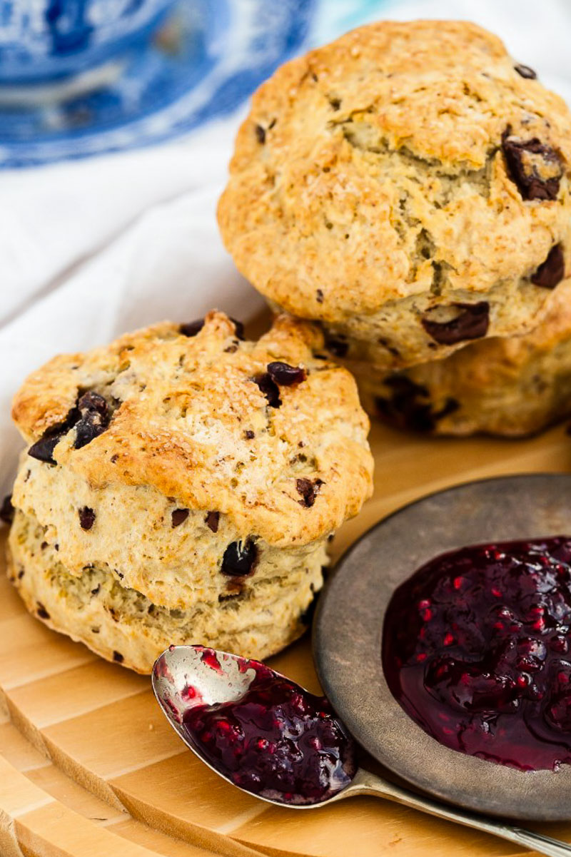 two scones and raspberry jam on wooden board