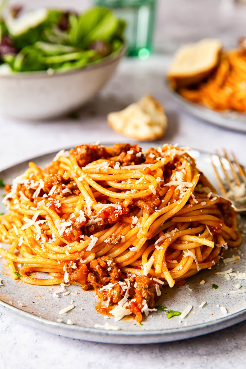 spaghetti bolognese on grey plate with salad in the background