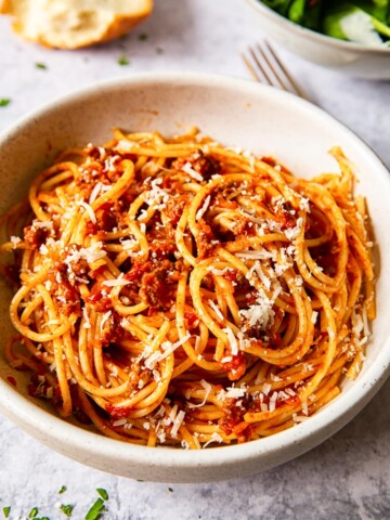 spaghetti bolognese sprinkled with Parmesan in cream bowl