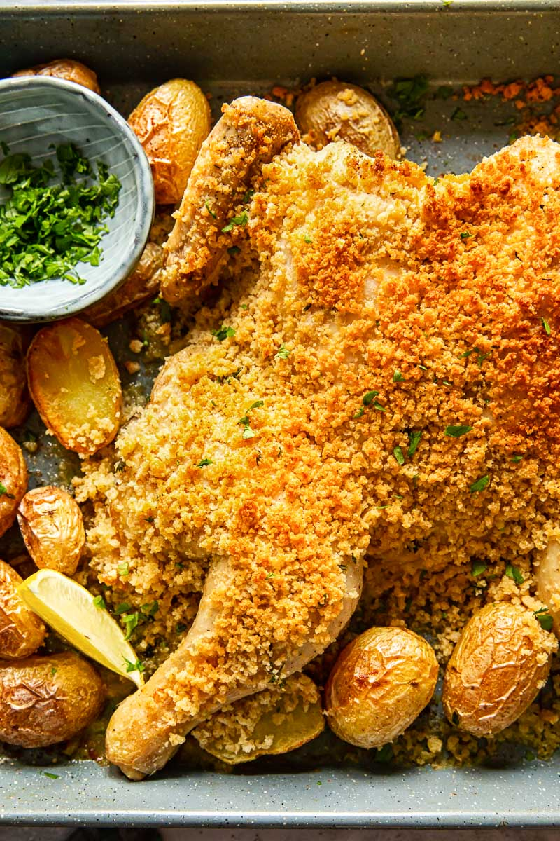 butterflied chicken in breadcrumbs and potatoes on grey pan
