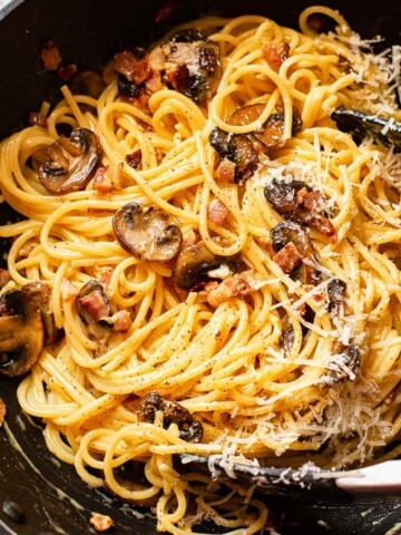 spaghetti carbonara with mushrooms in a pan
