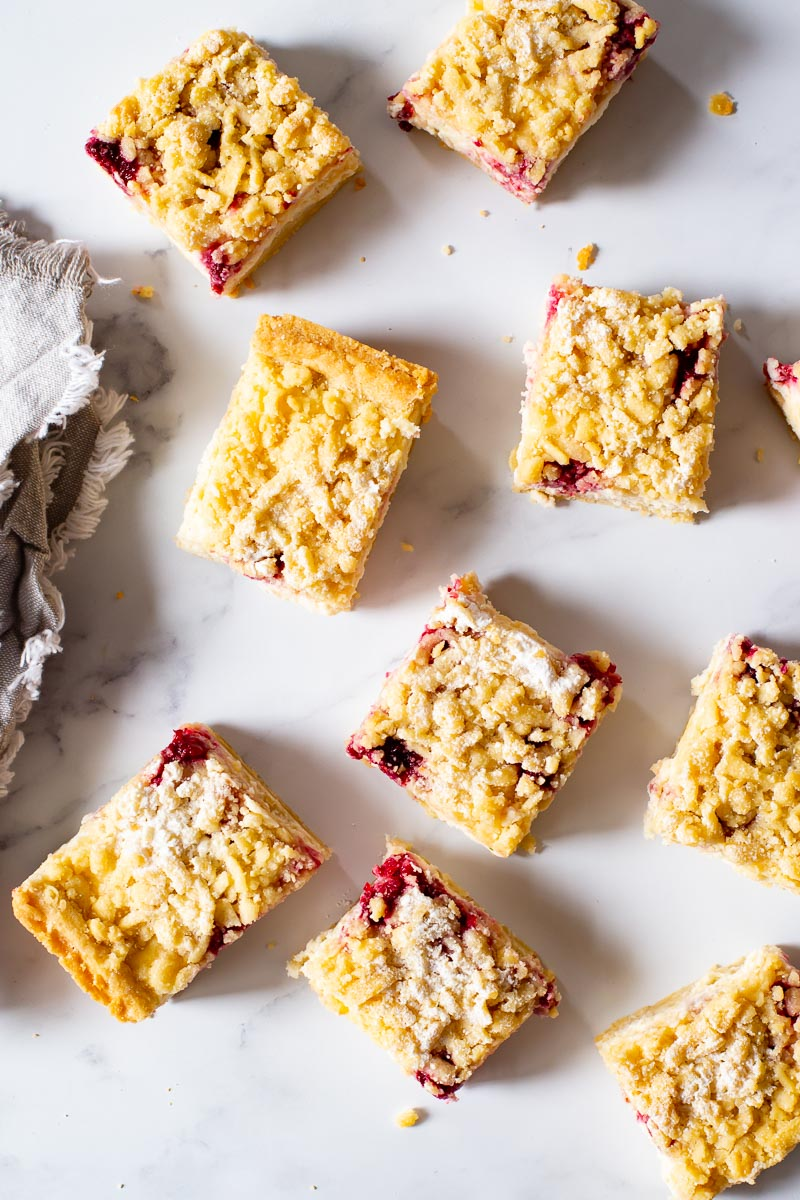 raspberry cheesecake bars on white background. Overhead view.