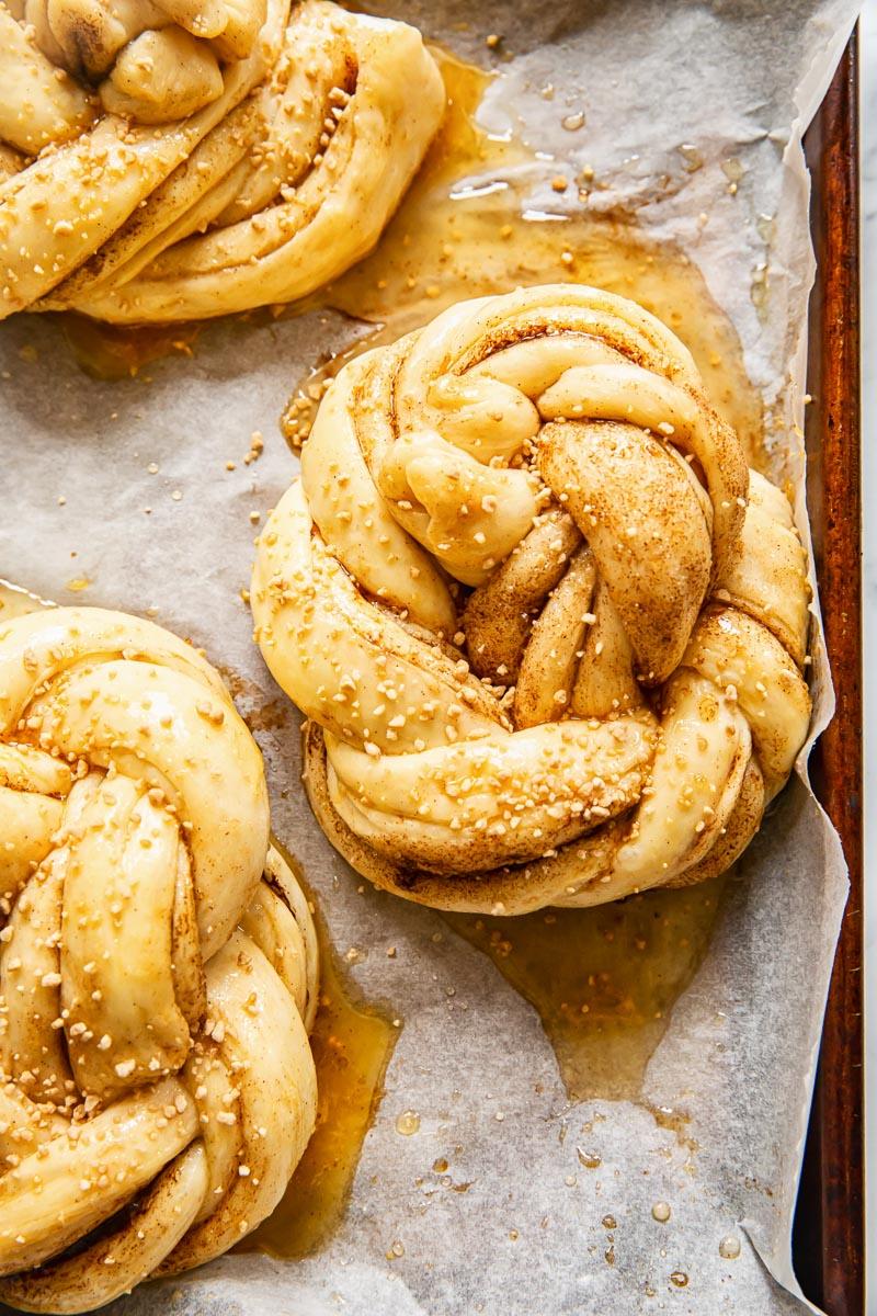 unbaked cinnamon buns on baking sheet