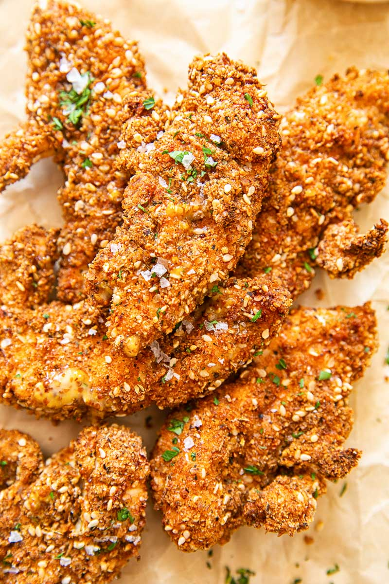 Chicken fingers in crispy coating on brown paper