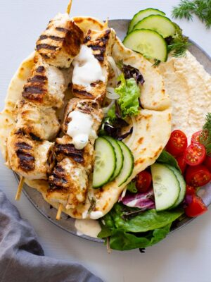 chicken souvlaki skewers on top of pita bread filled with hummus and vegetables
