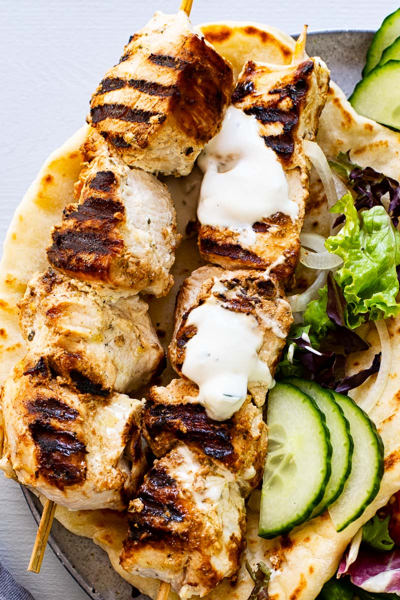 two chicken skewers on top of flatbread drizzled with yogurt