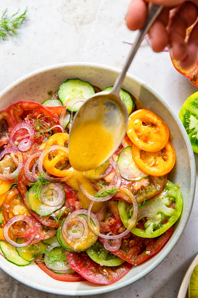 cucumber and tomato salad with a spoonful of salad dressing being poured on it