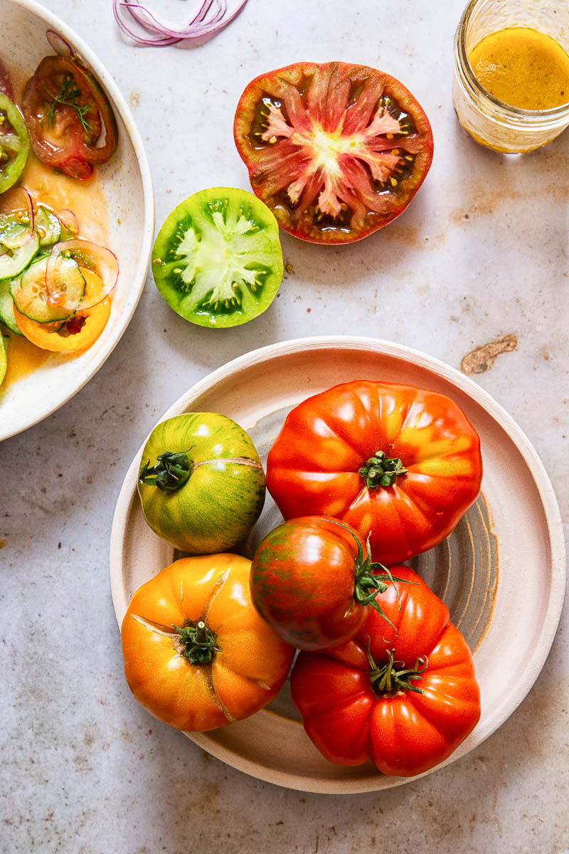 heirloom tomatoes on a plate, cut red and green tomatoes and salad dressing