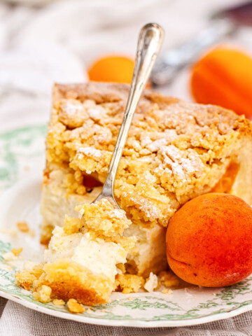 Apricot cheesecake with crumb topping on a plate with a fresh apricot next to it