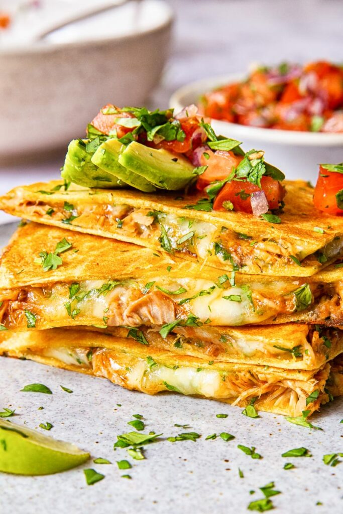 quesadilla pieces stacked on top of each other and topped with avocado and pico de gallo