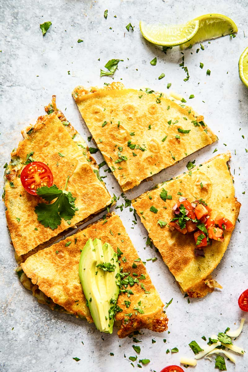 cheese quesadilla cut into quarters and topped with sliced avocado and pico de gallo on grey surface