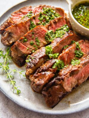 sliced rib eye steak with herb sauce on grey plate