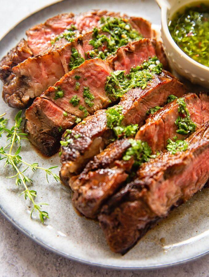 sliced rib eye steak with herb sauce on grey plate